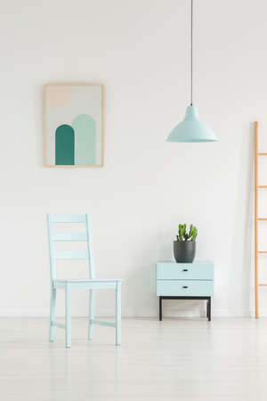 Photo pour Sky blue living room interior with a chair, cabinet, lamp and painting. Real photo - image libre de droit