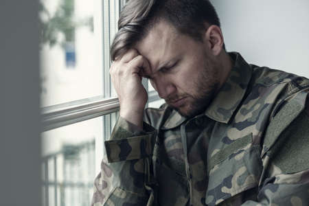 Foto de Depressed and lonely soldier in military uniform with war syndrome - Imagen libre de derechos