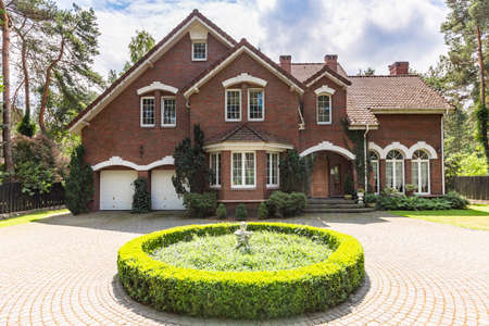 Photo for Front view of a red brick English style classic house with a steep roof, large windows and a circular driveway with a flowerbed decoration in the front. - Royalty Free Image