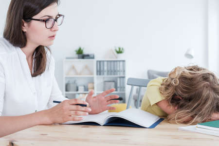 Foto de Tutor trying to talk to her angry pupil during a private lesson - Imagen libre de derechos