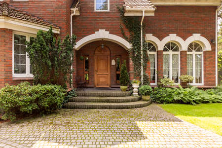 Photo pour Cobbled path and steps leading to a stylish entryway with ornamented wooden door and side windows in a red brick English style mansion. - image libre de droit