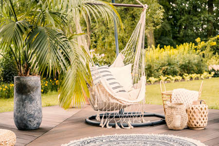 Foto de Summer in the green garden with a hammock and a palm tree on a terrace. - Imagen libre de derechos