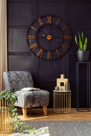 Photo for Big clock on the black wall, armchair, table and plant in a living room interior. Real photo - Royalty Free Image