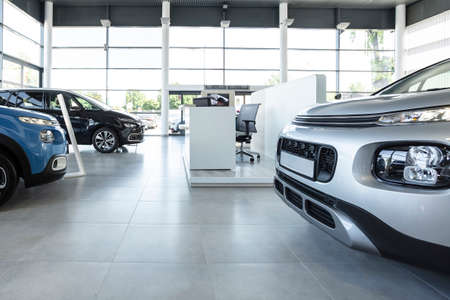 Photo for Car seller's station and parked cars in the interior of a modern dealership - Royalty Free Image