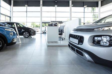 Foto de Car seller's station and parked cars in the interior of a modern dealership - Imagen libre de derechos