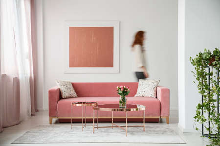 Foto de Blurred person against the wall with painting in white flat interior with plant and millenial pink couch. Real photo - Imagen libre de derechos