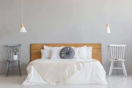 Foto de Blanket on wooden bed between chairs in grey bedroom interior with lamps and plant. Real photo - Imagen libre de derechos