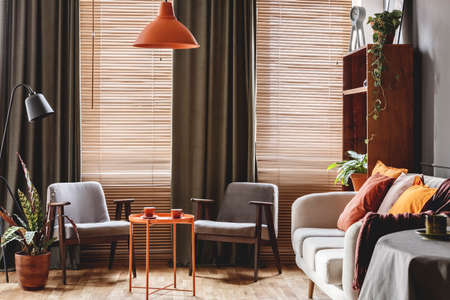 Photo pour Grey armchair at orange table in dark retro living room interior with drapes and blinds - image libre de droit