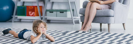 Foto de Panorama of bored autistic boy on carpet during meeting with psychotherapist - Imagen libre de derechos