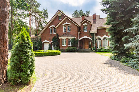 Photo pour Large cobbled driveway in front of an impressive red brick English design mansion surrounded by old trees - image libre de droit
