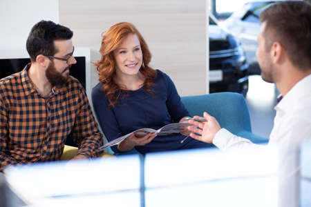 Photo for Couple looking at car offer and talking to a dealer in a car showroom - Royalty Free Image