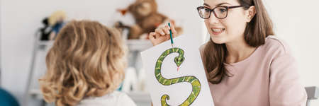 Foto de Panorama of woman teaching the child the alphabet with snake picture - Imagen libre de derechos