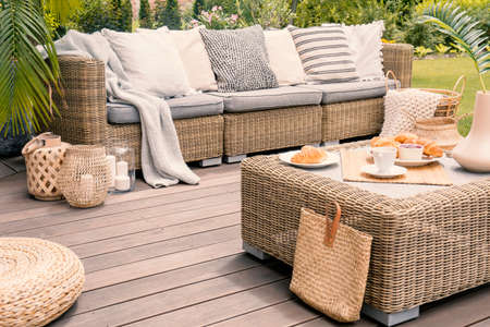 Photo pour Wicker patio set with beige cushions standing on a wooden board deck. Breakfast on a table on a backyard porch. - image libre de droit