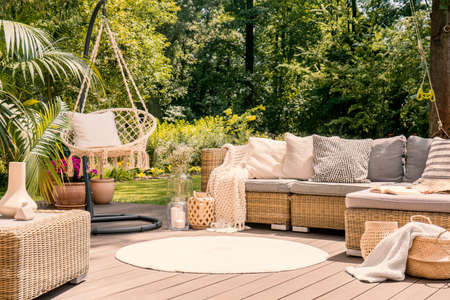 Photo for A big terrace with a comfortable leisure sofa with cushions, a table and a string swing in a green garden during sunny vacation. - Royalty Free Image