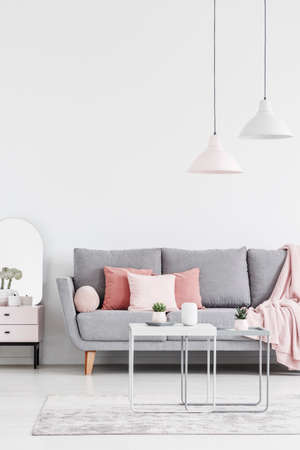 Foto de Lamps above table on carpet in white living room interior with pink pillows on grey sofa. Real photo - Imagen libre de derechos