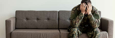 Foto de Soldier in uniform sitting on a sofa, waiting for his his appointment with a psychotherapist - Imagen libre de derechos