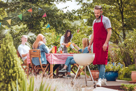 Photo for A young man wearing a burgundy apron cooking on a white grill. People sitting around a table and having fun during a celebration in the backyard. - Royalty Free Image