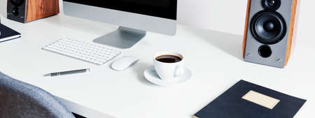 Photo for Close-up on a cup of coffee next to a computer mouse and keyboard on white desk in an interior for a freelancer. Real photo - Royalty Free Image