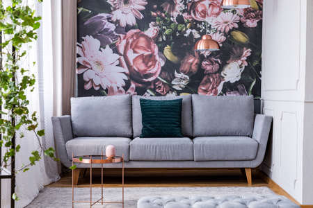 Photo pour Copper table on carpet and green pillow on grey couch in flowers living room interior. Real photo - image libre de droit