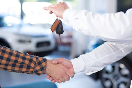 Photo for Close-up of two men shaking hands after making a deal. Seller holding car keys - Royalty Free Image