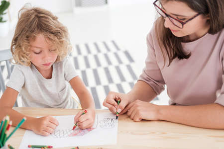 Foto de Little kid drawing a house using colorful crayons with his female, therapist during a meeting in the office - Imagen libre de derechos