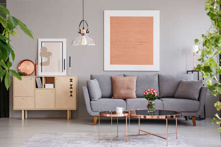 Photo pour Real photo of a wooden cupboard next to a sofa in a modern living room interior with a big painting - image libre de droit