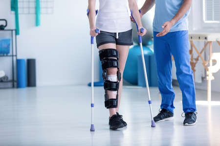 Photo pour Sport physiotherapist and patient with leg injury during training with crutches - image libre de droit