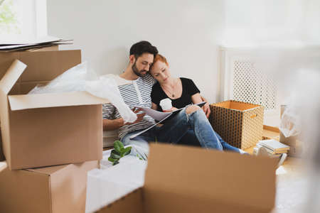 Photo for Happy marriage packing stuff into carton boxes while moving-out - Royalty Free Image