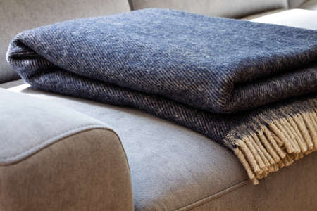 Foto de Close-up of a warm, navy blue, wool blanket with beige fringe on a comfy, gray sofa in a cozy living room interior - Imagen libre de derechos