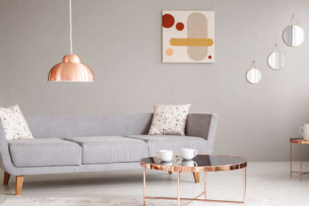 Foto de Real photo of a simple sofa, copper lamp and table, and painting on a wall in a living room interior - Imagen libre de derechos
