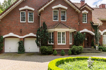 Foto de Real photo of a brick house with a bay window, garages and round garden in front of the entrance - Imagen libre de derechos