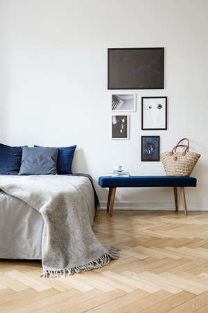 Foto de Grey blanket on bed with blue pillows in white bedroom interior with posters above bench. Real photo - Imagen libre de derechos