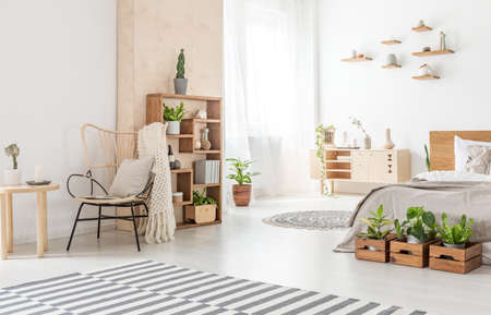 Photo pour Armchair next to wooden table and carpet in bedroom interior with plants in front of bed. Real photo - image libre de droit