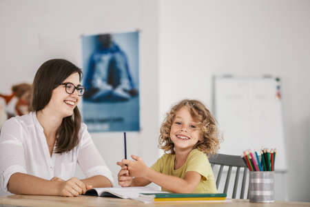 Foto de Smiling teacher and happy kid doing homework after classes - Imagen libre de derechos