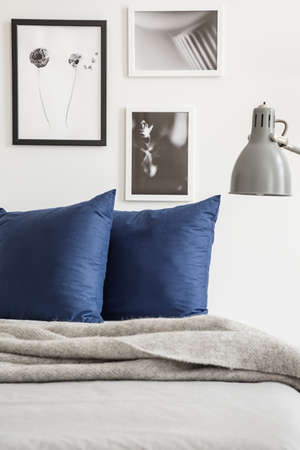 Foto de Grey blanket and navy blue cushions on bed in bedroom interior with posters and lamp. Real photo - Imagen libre de derechos