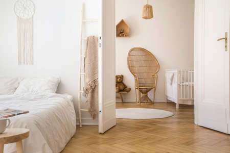 Photo pour White apartment interior with herringbone parquet, double bed and open door to kid room with peacock chair, white crib and round rug on the floor - image libre de droit