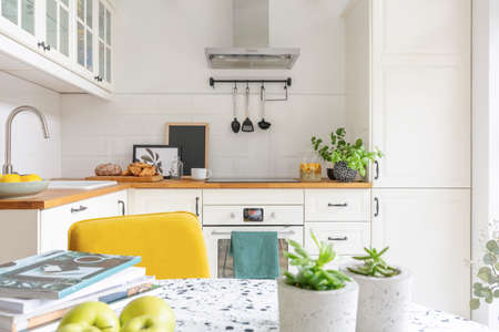 Foto de Close-up of a table with fruit, plants and magazines in a bright kitchen interior. Cupboards in the background. Real photo - Imagen libre de derechos