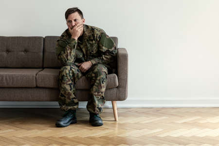 Foto de Depressed professional soldier in green uniform sitting alone at home. Copy space on the wall - Imagen libre de derechos