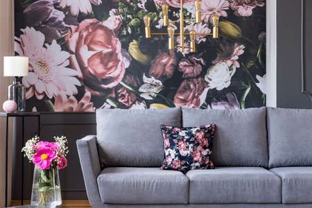 Foto de Real photo of a flower print behind a couch in a living room interior with fresh flowers in a vase - Imagen libre de derechos