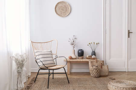 Photo pour Flowers on wooden stool next to armchair in white loft interior with pouf and plate. Real photo - image libre de droit