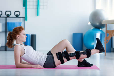 Foto de Sportswoman on mat doing exercises with broken leg during rehabilitation - Imagen libre de derechos