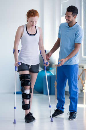 Photo pour Physiotherapist helping woman with stiffener on the leg walking with crutches - image libre de droit
