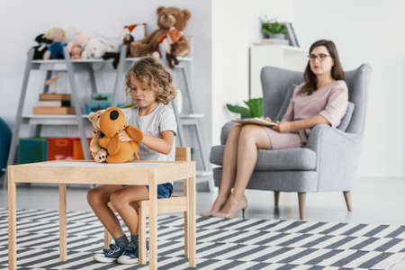 Foto de Unbearable boy playing with plush toy and psychotherapist analyzing his behavior - Imagen libre de derechos