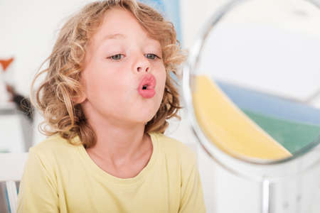 Photo pour Kid learning to speak in front of a mirror during correct pronunciation classes - image libre de droit