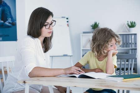 Foto de Naughty boy doing homework with mother after classes - Imagen libre de derechos