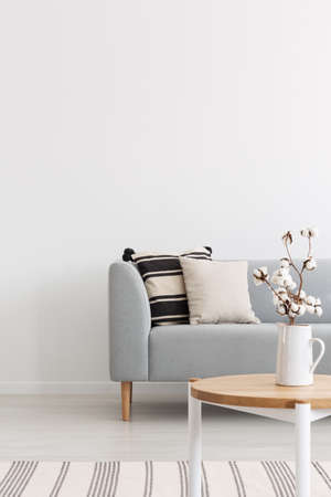 Foto de Flowers on wooden table in white minimal flat interior with pillows on grey sofa near rug. Real photo - Imagen libre de derechos
