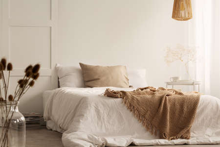 Photo for Flowers and lamp in white natural bedroom interior with blanket and pillows on bed. Real photo - Royalty Free Image