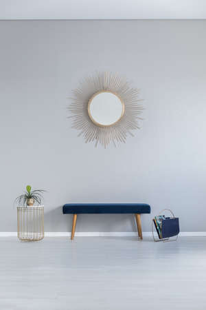 Photo pour Gold mirror on the wall above blue bench in grey minimal entrance hall winterior ith table. Real photo - image libre de droit