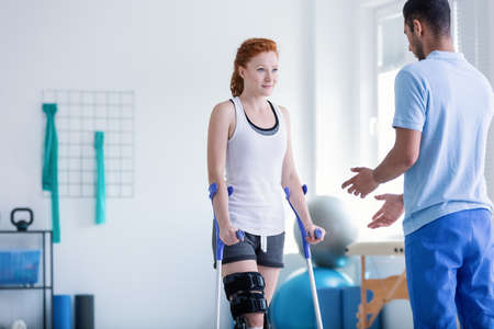Foto de Woman with crutches during rehabilitation with helpful physiotherapist - Imagen libre de derechos