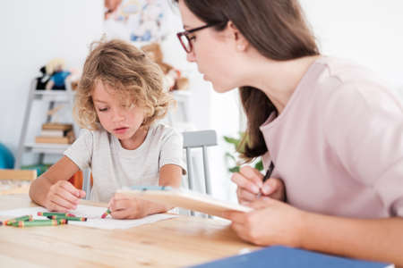 Foto de A psychotherapist watching a child draw pictures with crayons during an evaluation in a private school. - Imagen libre de derechos